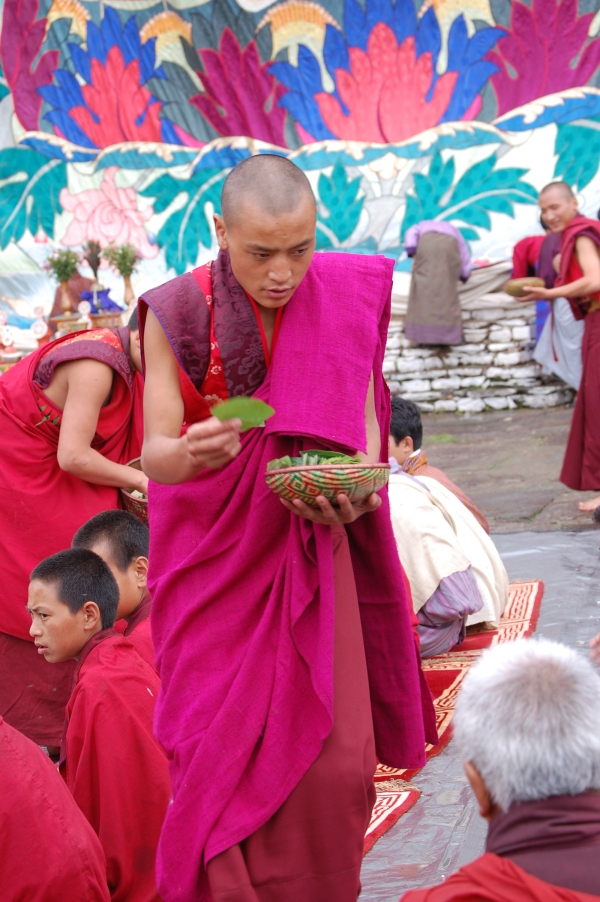 Monk passing out betel leaves to the guests